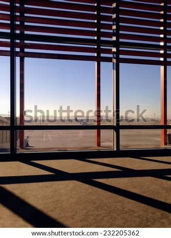 Window view to runway with two passenger aircrafts inside of the modern airport terminal with sun protection lattice and shadow during sunset.