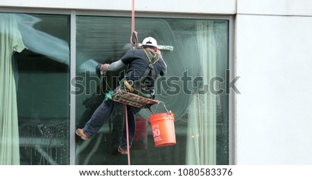 Window washer cleaning building facade. Person cleaning building window Foto stock ©
