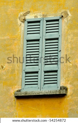 window with a closed shutter in a wall covered in faded paint in Italy