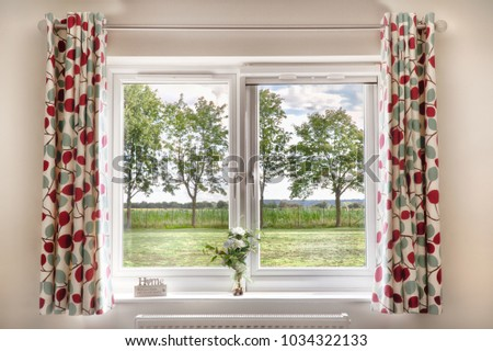 Window with a view onto fields and trees in a rural setting. Curtains and a bright summers day make this a beautiful scene and a place anyone would love to live