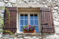 window with brown shutters and colorful flowers on the window sill