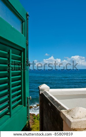Window with green shutters overlooking the sea