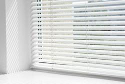 Window with open modern horizontal blinds indoors, closeup