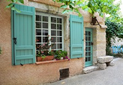 Window with open shutters and door in provence style and tiffany color with original lantern in the form of an old inverted watering can over the door