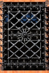 Window with ornate curly metal grid on religious building in Milan on sunny day. Exterior part of antique church. Vintage picturesque window in european city. European architecture