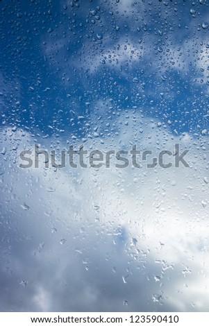 Window with raindops and blue sky