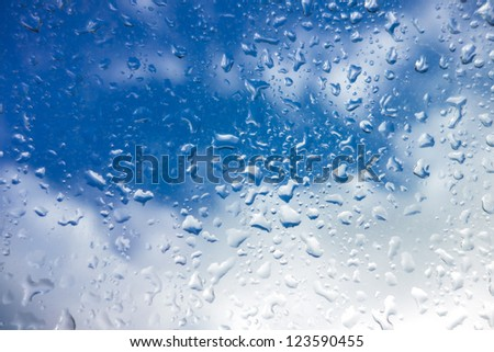 Window with raindops and blue sky