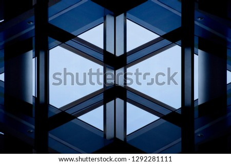 Windows and glass wall with metal framework. Abstract modern architecture background with geometric structure. Close-up photo of office building fragment in shadows against clear blue sky.  #1292281111