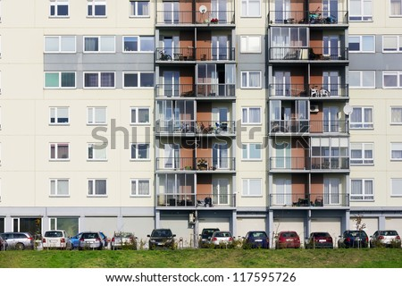 Windows, balconies, cars and green grass lawn  of a multiroom apartment house of mass standard building town. Sunny autumn day.