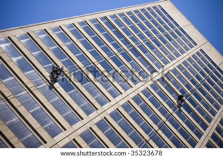 windows cleaners working on  modern building / abstract architectural background