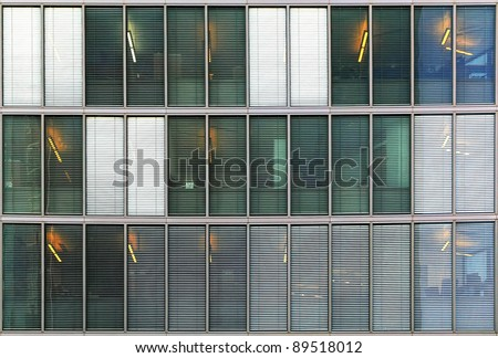Windows of a modern office building with shutters - stock photo