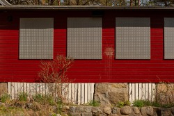 Windows of a red house boarded up with metal plates