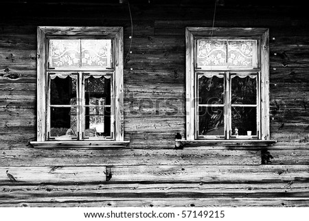 Windows of old, wooden cottage in the countryside in black and white