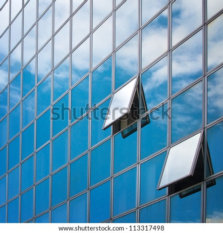 Windows of the modern office building with clouds reflecting. Modern business architecture.