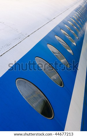 Windows of the white airplane fuselage with blue line