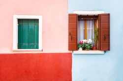 Windows on the red and blue painted facade of the house. Colorful architecture in Burano island, Venice, Italy.
