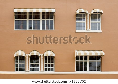 Windows with awnings on a brown wall