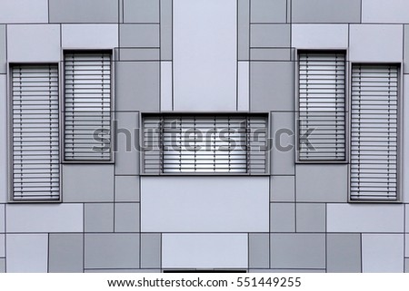 Windows with blinds / jalousie / louvers on a modular metal wall. Fragment of office building exterior in metallic gray color. Abstract black and white photo of modern architecture.
