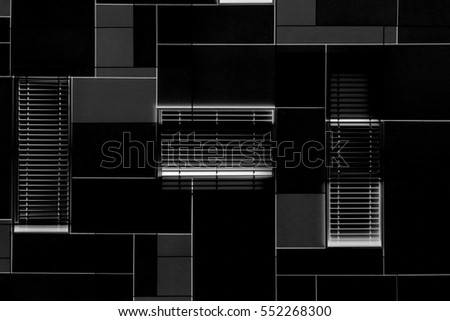 Windows with blinds / louvers on a modular metal wall in darkness. Grunge photo of office building exterior. Abstract black and white image of hi-tech architecture. Modern architectural background.