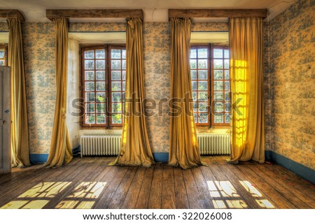 Windows with yellow curtains in an abandoned castle, HDR processing