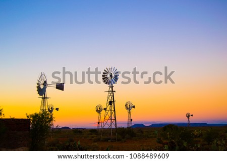 Windpumps and a sunset on a farm located in the karoo in South-Africa