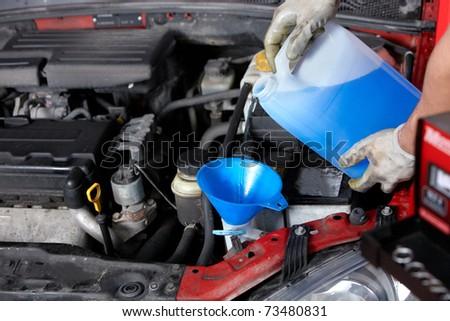 Windscreen washer. Mechanic working in auto repair shop.