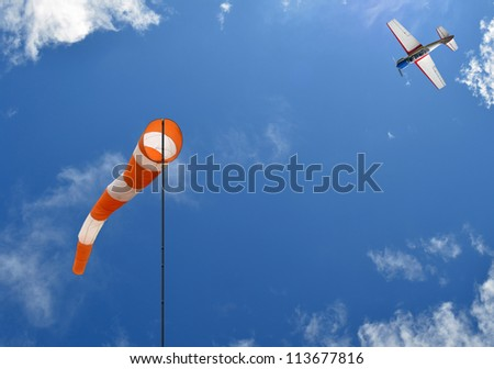 Windsock and airplane in blue sky