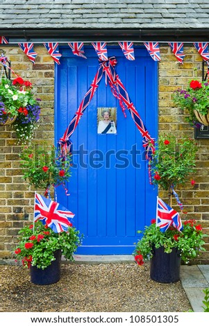 WINDSOR, UK - CIRCA JUNE 2012: Blue door decorated with an image of Queen Elizabeth II and union jack bunting for part of the Queens Diamond Jubilee celebrations circa June 2012.