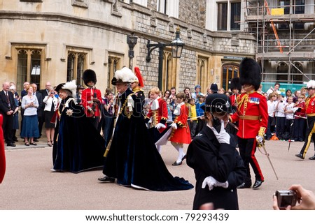 WINDSOR, UK- JUNE 13: Her Majesty Queen Elizabeth and Prince Phillip Duke of Edinburgh, in the robes of the Most Noble Order of the Garter with page boys. Windsor Castle June 13, 2011 in Windsor UK