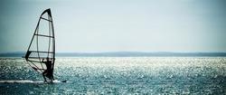 windsurfer panorama silhouette against a sparking blue sea