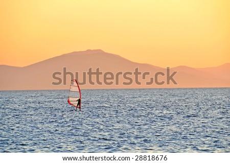 windsurfer sailing against the sunset