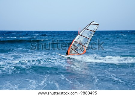 windsurfer sailing away form the beach on blue waters