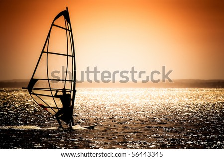 windsurfer silhouette against a sunset background - natural blue sky version available - image ref 56118271