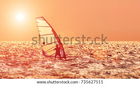 Windsurfer silhouette against a sunset background. Windsurfer Surfing The Wind On Waves, Recreational Water Sports, Extreme Sport Action. Sporting Activity. Healthy Active Lifestyle. Summer Fun