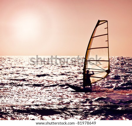 Windsurfer silhouette over sea sunset, beautiful beach landscape, summertime fun, sport, activities, vacation and travel concept
