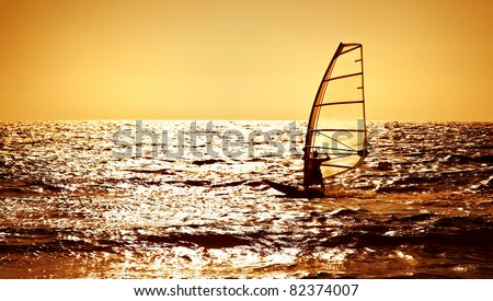 Windsurfer silhouette over sea sunset, panoramic beach landscape, summertime fun, sport, activities, vacation and travel concept