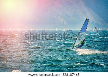 Windsurfer Surfing The Wind On Waves In Garda Lake, Recreational Water Sports, Extreme Sport Action. Recreational Sporting Activity. Healthy Active Lifestyle. Summer Fun Adventure. Hobby
