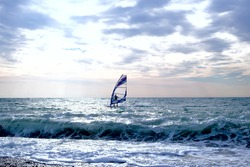 Windsurfer surfing through wavy sea with sail board. Lifestyle and sport concept. Fun and leisure activity.