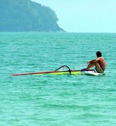 Windsurfer waiting for Wind. Malaysia coast.
