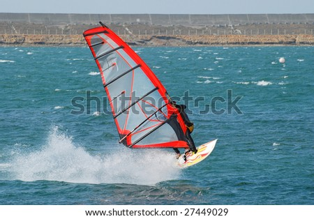 windsurfer with bright colored sail on Algarve blue water