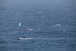 Windsurfing and kitesurfing face to face surfing at high speed in the waves of the Pacific Ocean. Both windsurfer and kitesurfer silhouettes are cut out over the blue sea water