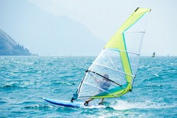 Windsurfing on Lake Garda. Unidentifiable Windsurfer Surfing The Wind On Waves, Recreational Water Sports, Selective focus