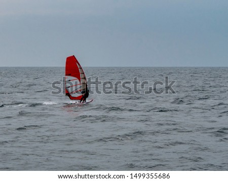 Windsurfing on the Black Sea. Water fun. Kind of sport. Overcast weather. Windsurfer on a board under a red sail. #1499355686