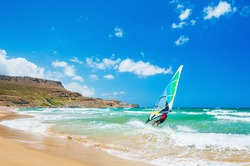 Windsurfing on the sea coast. Tropical beach with turquoise water and big waves. Crete island, Greece.
