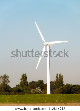 Windturbine on grass field with trees in background
