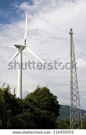 Windturbine producing alternative energy with a blue sky - stock photo