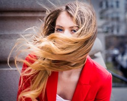Windy Day. Dressing in red, a young woman with long blonde hair is on a windy day.