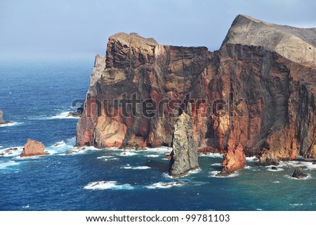 Windy day on ocean island Madiera. Bright red and gray coastal rocks of east part of island