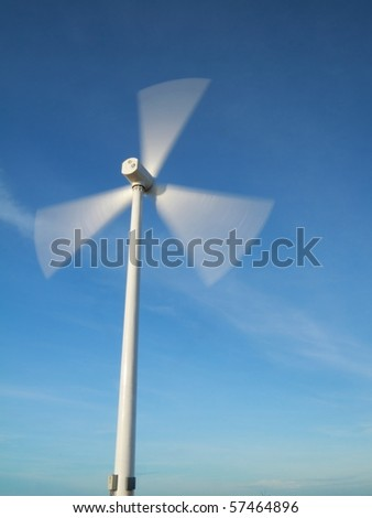 windy day with motion blade of modern wind turbine.