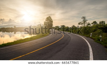 Windy road through forest and lake lead to sunrise